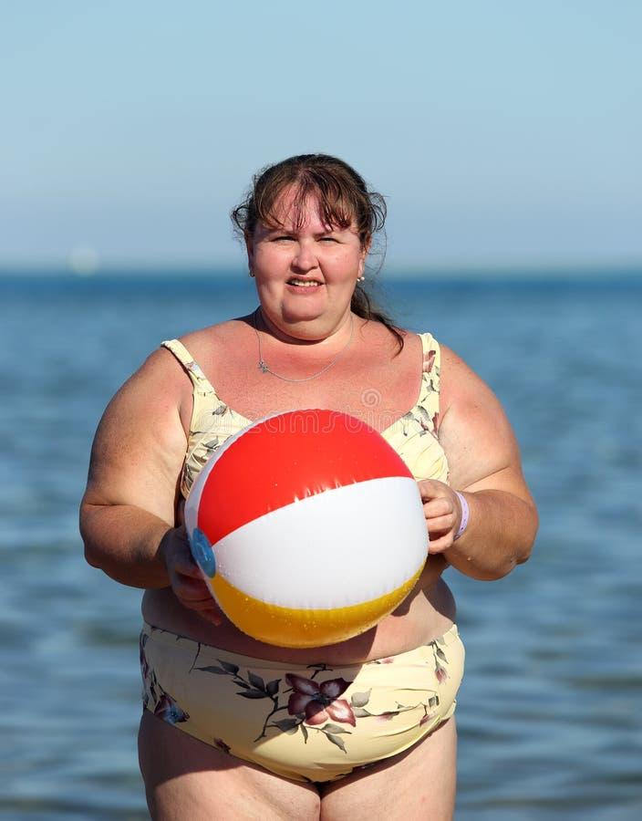 Överviktig kvinna med bollen på stranden arkivfoton