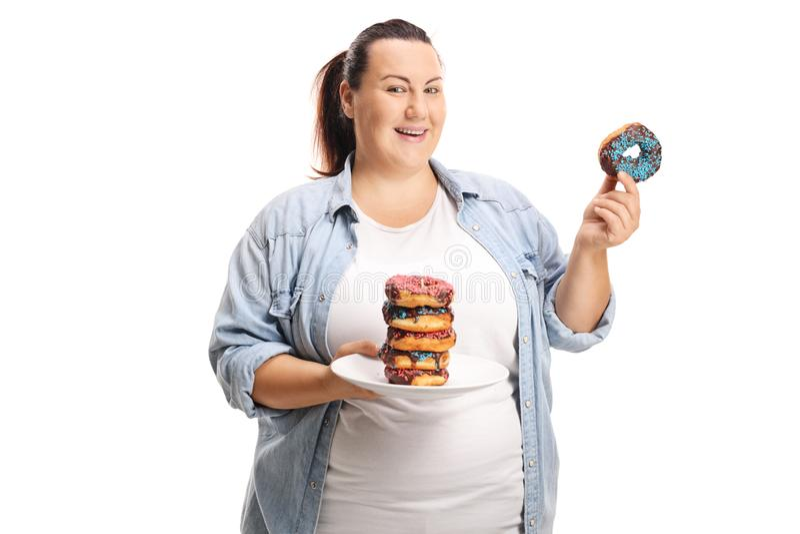 Överviktig kvinna med en hög av donuts som isoleras på vit bakgrund arkivfoto