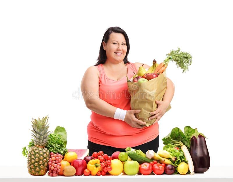 Överviktig kvinna med en livsmedelpåse bak en tabell med frukt royaltyfria bilder