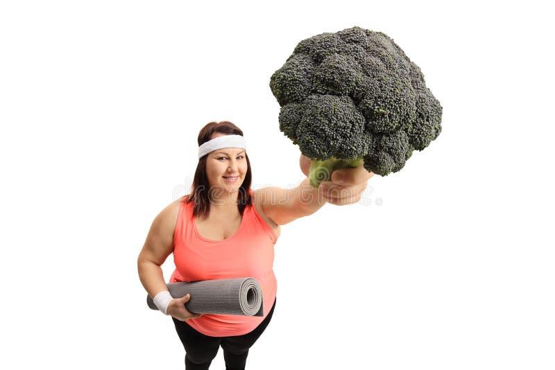 Överviktig kvinna med en matt övning och broccoli arkivbild