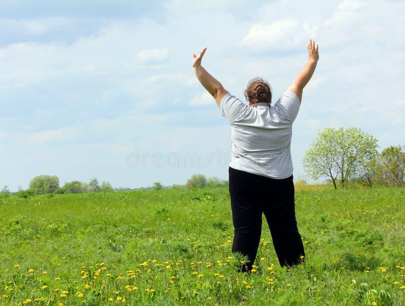 Överviktig kvinna med händer upp på äng arkivfoton