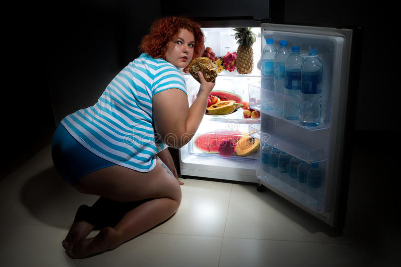 Överviktig kvinna med kylskåpet arkivfoton