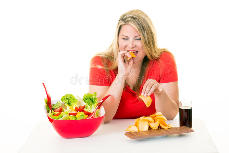 Överviktig kvinna som äter sjuklig skräpmat royaltyfri foto