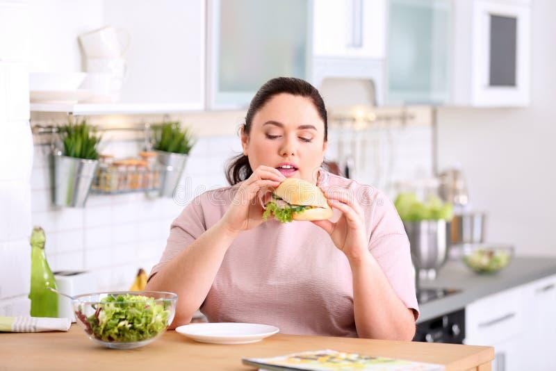 Överviktig kvinna som äter smörgåsen i stället för sallad på tabellen i kök royaltyfri bild
