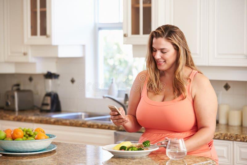 Överviktig kvinna som äter sunt mål och använder mobiltelefonen royaltyfria bilder