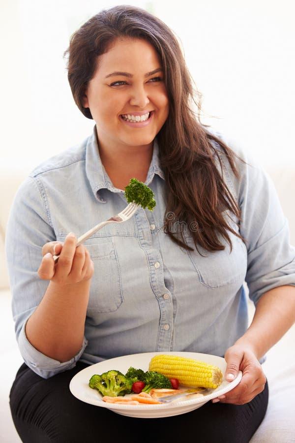 Överviktig kvinna som äter sunt målsammanträde på soffan royaltyfri foto
