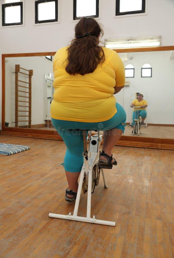 Överviktig kvinna som övar på cykelsimulatorn arkivfoto