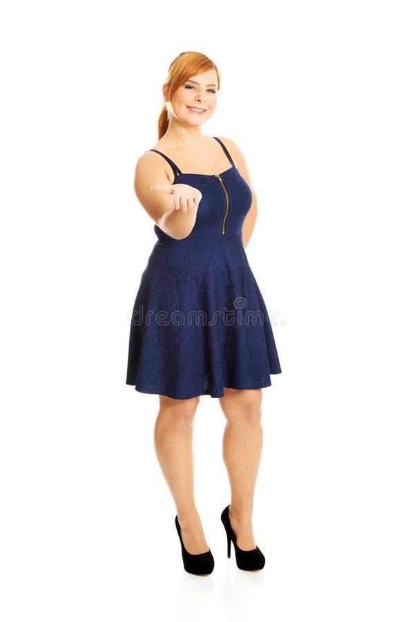 Överviktig kvinna som framlägger något arkivfoto