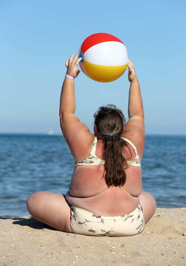 Överviktig kvinna som gör gymnastik på stranden arkivbild