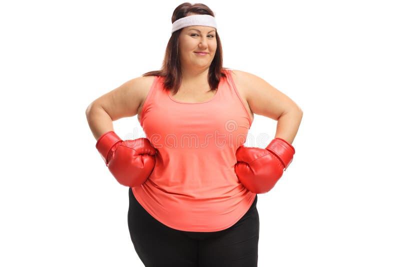 Överviktig kvinna som poserar med ett par av röda boxninghandskar fotografering för bildbyråer