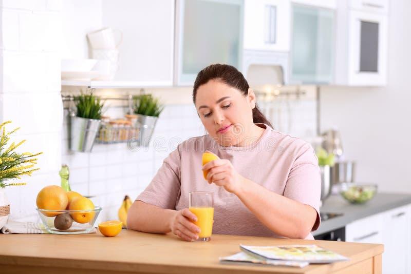 Överviktig kvinna som pressar orange fruktsaft in i exponeringsglas på tabellen i kök royaltyfri fotografi