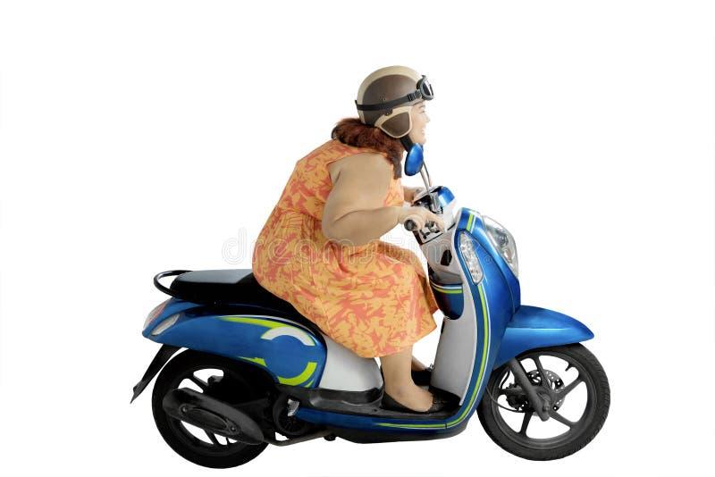 Överviktig kvinna som rider en moped på studio royaltyfri bild