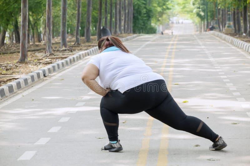 Överviktig kvinna som sträcker hennes ben på vägen arkivfoto