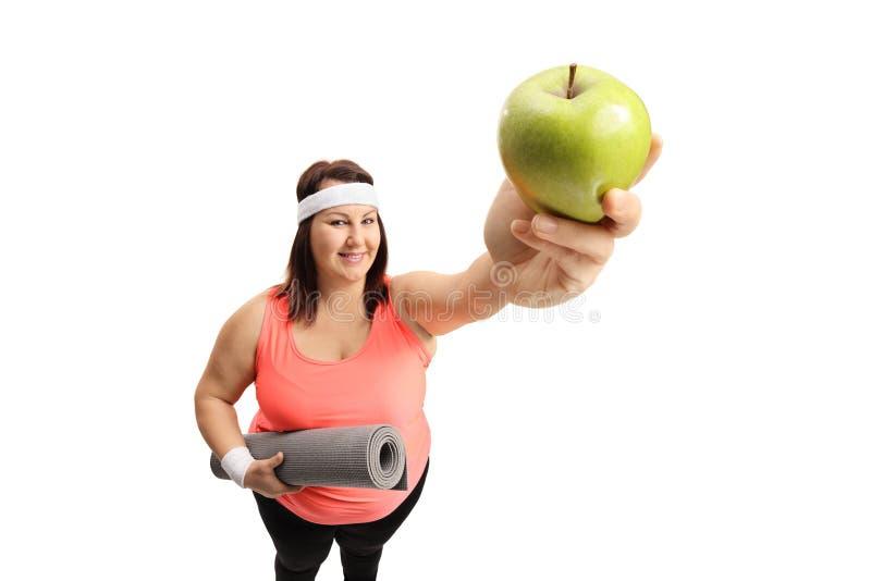 Överviktig kvinna som visar ett äpple fotografering för bildbyråer
