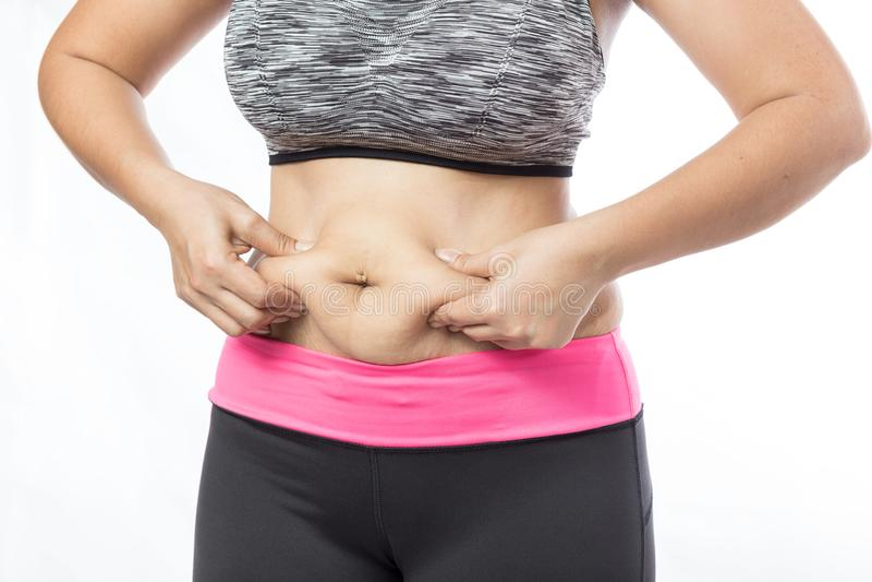 Överviktig kvinnahand som klämmer den överdrivna buken fet royaltyfria foton