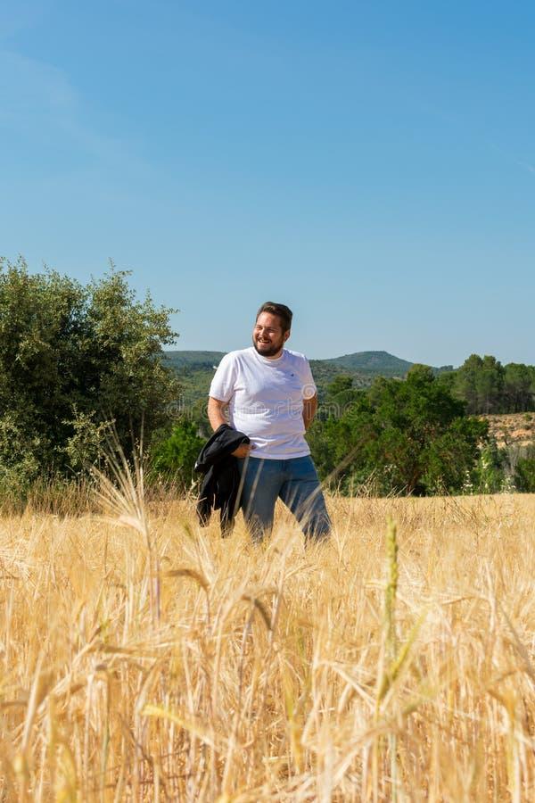 Överviktig man i ett fält i sommar arkivbilder