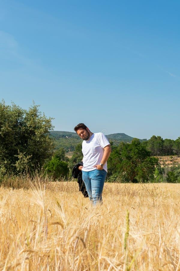 Överviktig man i ett fält i sommar arkivfoton