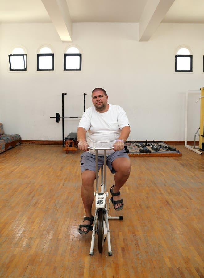 Överviktig man på cykelsimulatorn royaltyfri fotografi