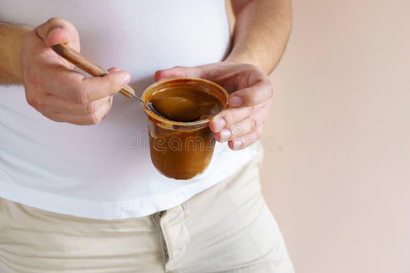 Överviktig man som äter jordnötsmör från kruset fotografering för bildbyråer