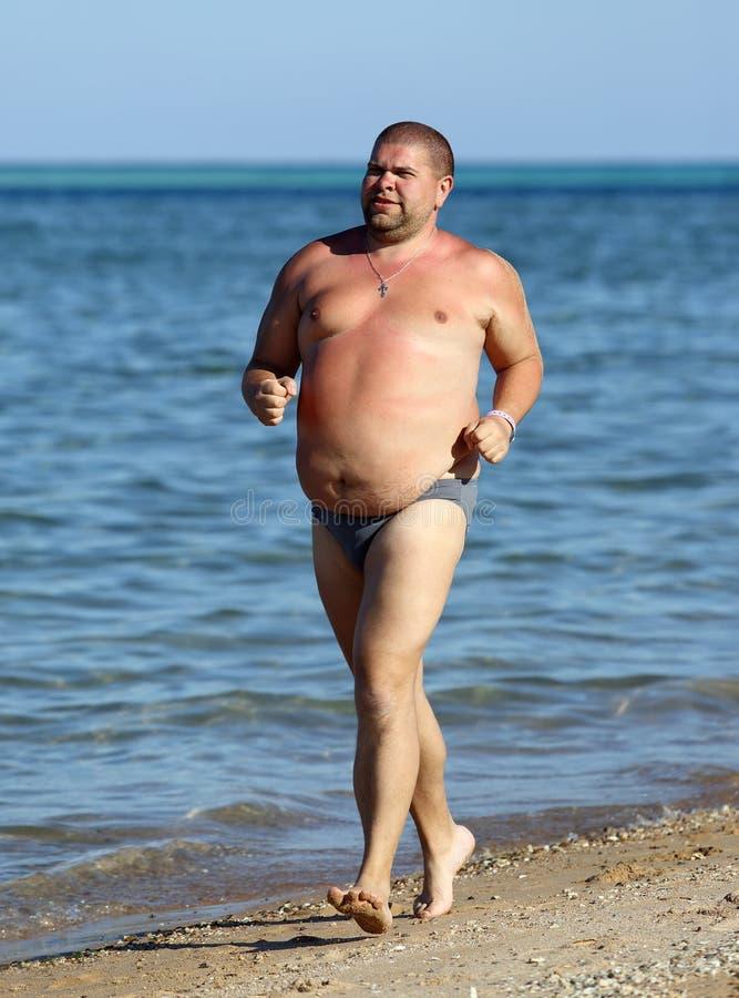 Överviktig manspring på stranden arkivfoton