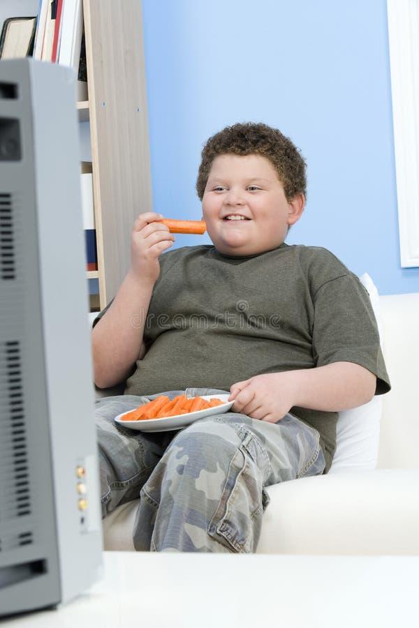 Överviktig pojke med morotpinnar i Front Of Television royaltyfria foton