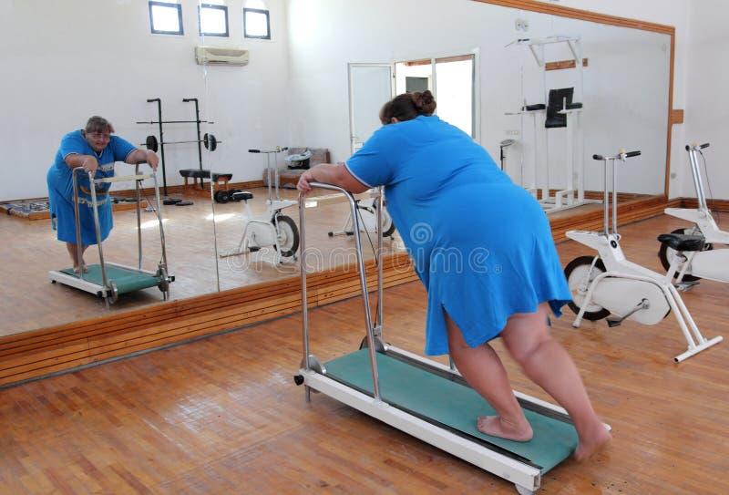 överviktig running instruktörtreadmillkvinna royaltyfri fotografi