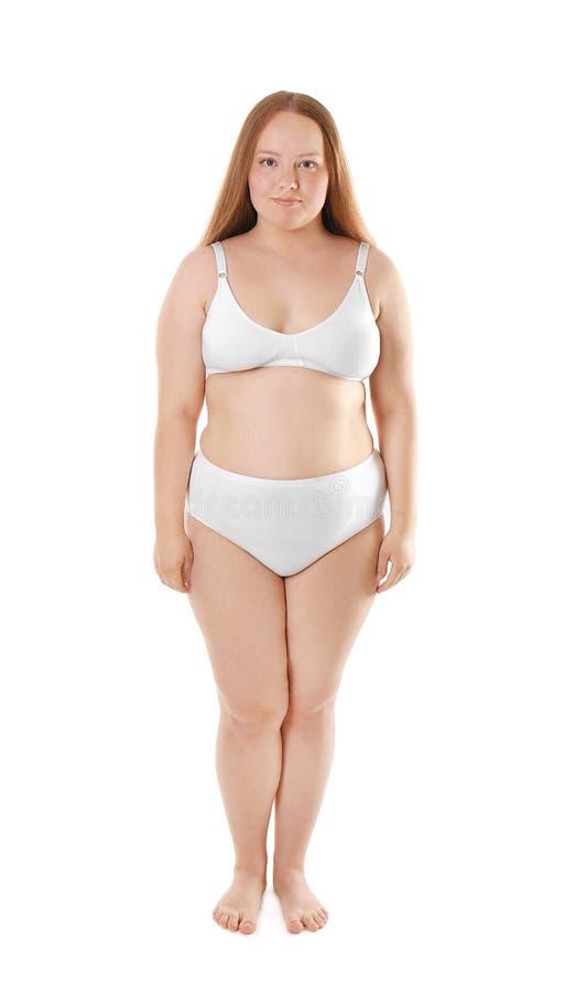 Överviktig ung kvinna i underkläder på vit bakgrund arkivbild