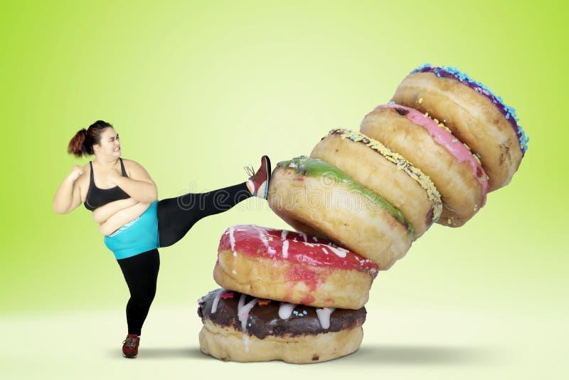 Överviktig ung kvinna som sparkar donuts royaltyfri fotografi