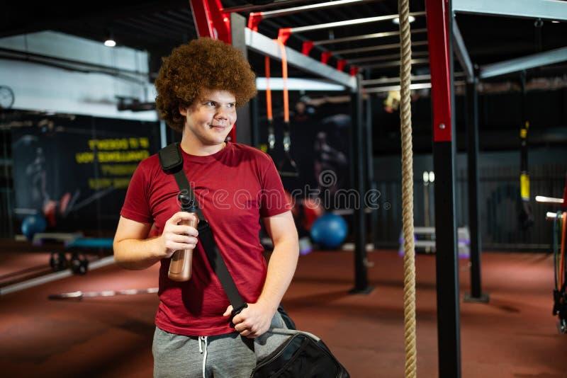 Överviktig ung man som tränar i gym för att uppnå mål arkivfoton
