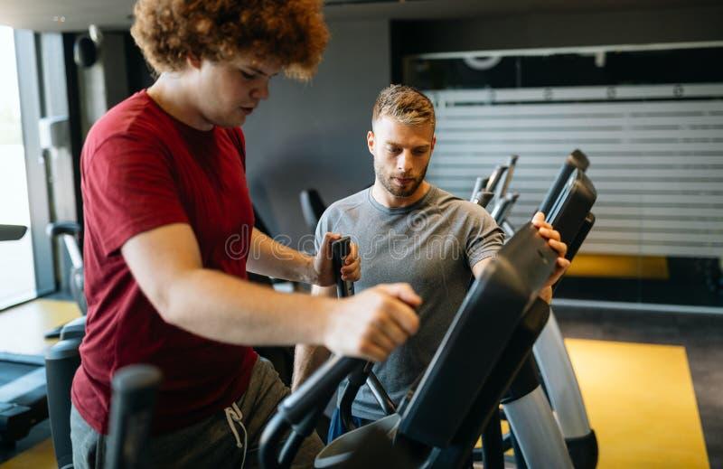Överviktig ung man som tränar i gymmet med personlig tränare arkivfoto