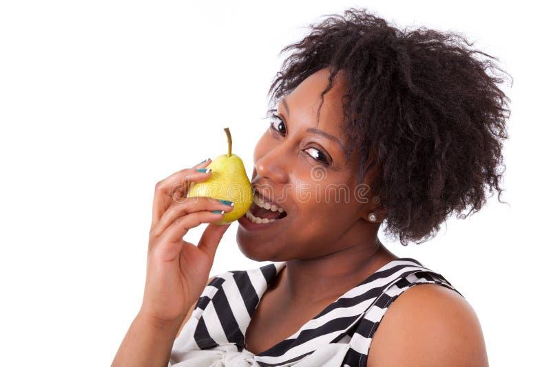 Överviktig ung svart kvinna som äter ett päron - afrikanskt folk royaltyfri foto