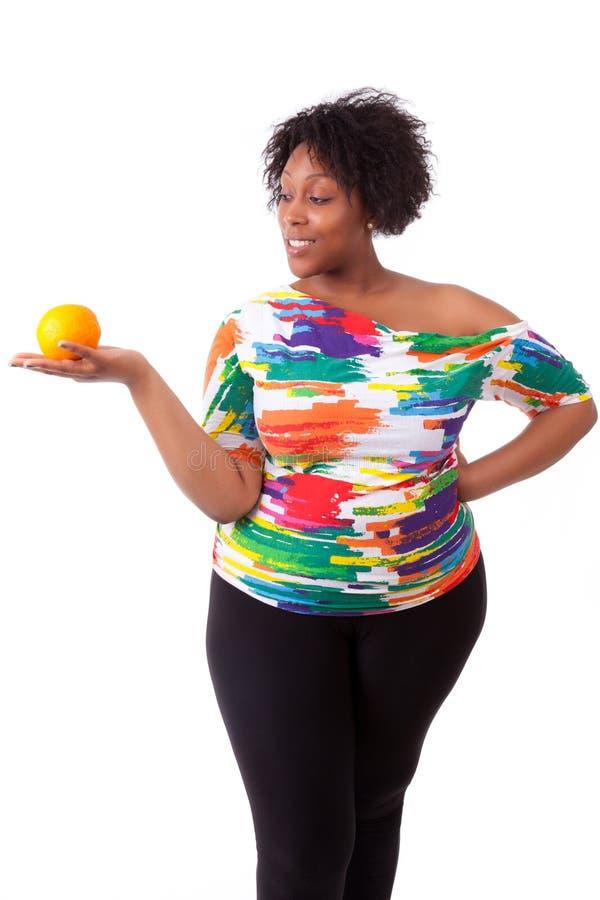 Överviktig ung svart kvinna som rymmer en apelsin - afrikanskt folk arkivbild