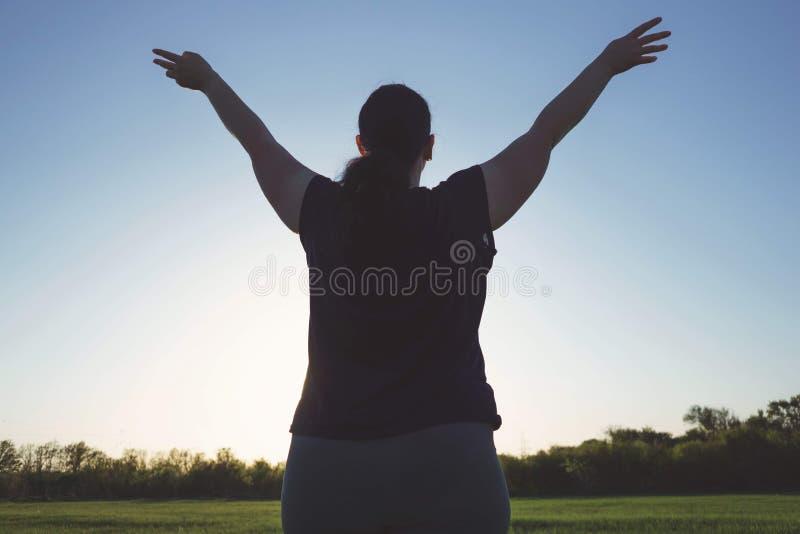 Överviktiga kvinnaresninghänder in mot himlen arkivfoto