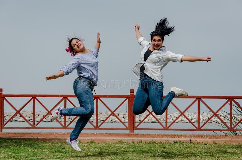 Överviktiga kvinnor som hoppar i parkera fritt avstånd arkivbild