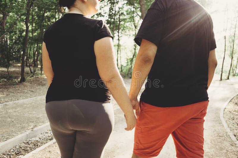 Överviktiga par som tillsammans går arkivfoto