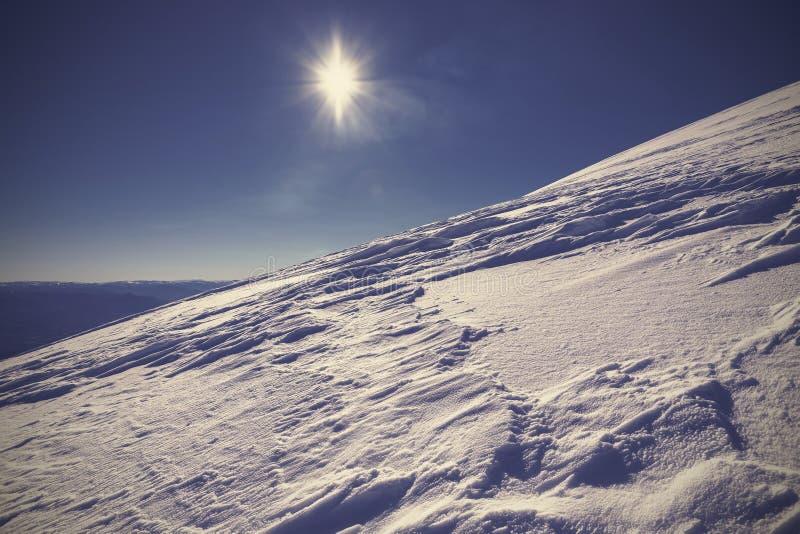 Övervintra berget som täckas med snö mot solen arkivbild