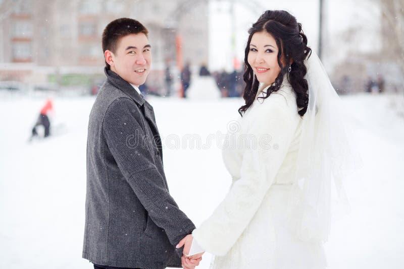 Övervintra bröllop-, brud- och brudguminnehavhänder som ser kameran, klassisk stående av par i den snöig gatan royaltyfri bild
