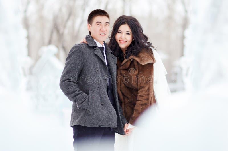 Övervintra bröllop, skyler ansar snöar bruden med, i vintrig kläder på gatan i mitt av isdiagram och fotografering för bildbyråer