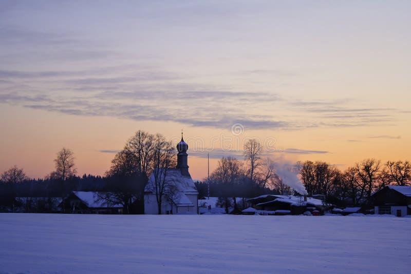 Övervintra den snöig byn på solnedgången, Bayern, Tyskland arkivbild
