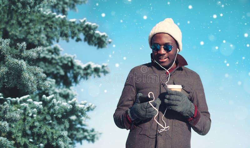 Övervintra den unga le afrikanska mannen som tycker om lyssnande musik på smartphonen med den pappers- koppen kaffe över snöfling royaltyfri bild