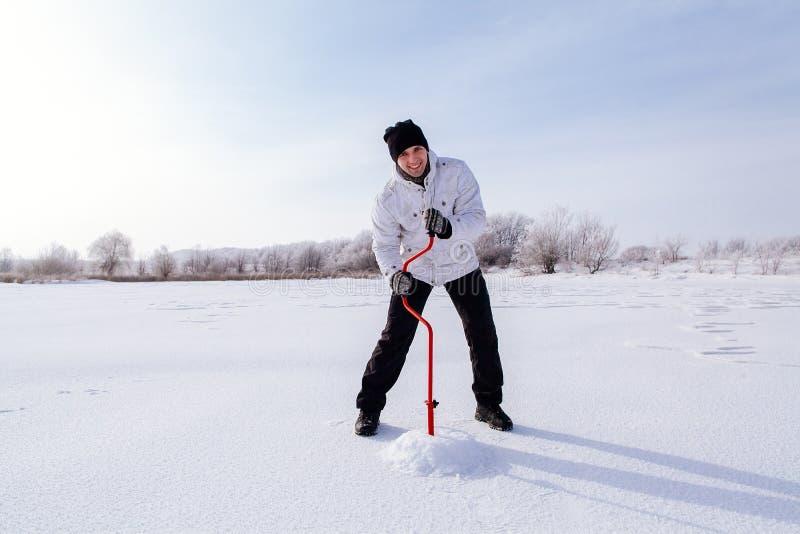 Övervintra fiskaren med isskruven på den djupfrysta sjön arkivfoton