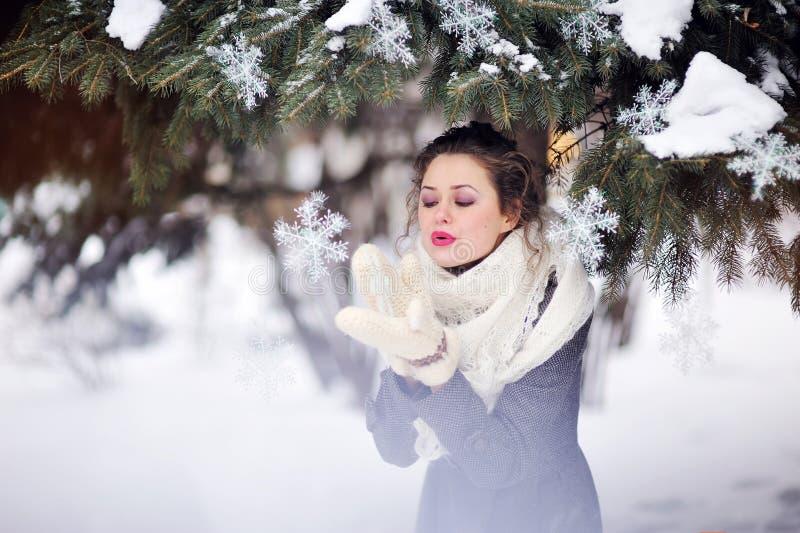 Övervintra flickan som blåser på en snöflinga i stack tumvanten arkivfoton