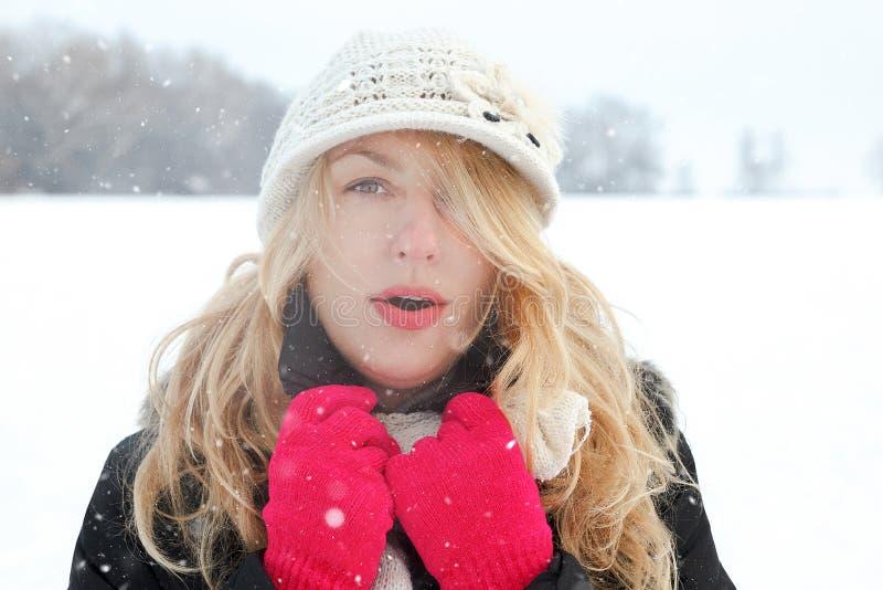 Övervintra kvinnan i snöfoto och att se och blåser andedräkt fotografering för bildbyråer
