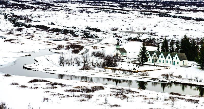 Övervintra landskapet av den små träkyrkan och hus på Thingvelli royaltyfri fotografi