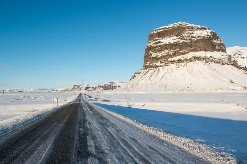 Övervintra landskapet, den icelandic huvudvägen och det härliga Lomagnupur berget royaltyfri fotografi