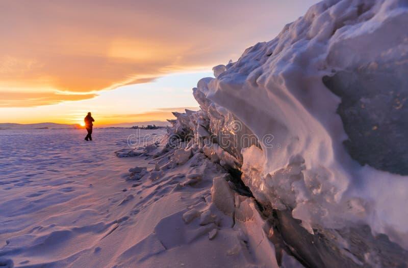 Övervintra landskapet i solnedgången, sprucken fryst is av sjön som täckas av snö på Lake Baikal, Ryssland i solnedgång royaltyfria bilder