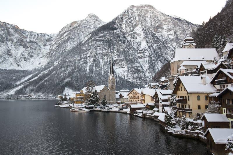 Övervintra landskapet med berg och lilla staden Hallstatt och den berömda kyrkan, Österrike royaltyfri foto