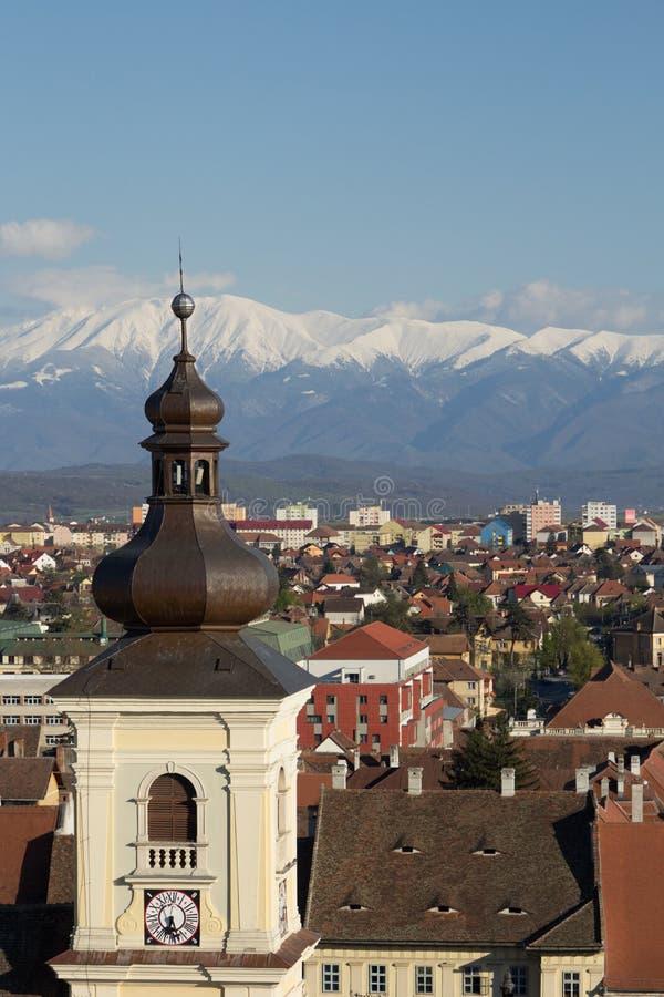Övervintra landskapet med ett torn i förgrunden och berg i bakgrunden royaltyfri fotografi
