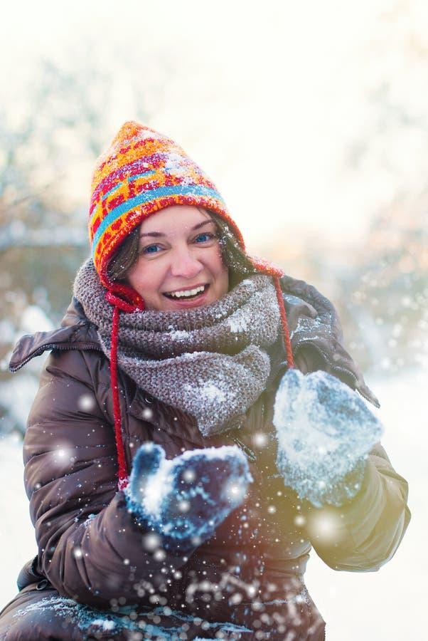 Övervintra livsstilbegreppet - den unga kvinnan som spelar med utomhus- snö arkivbild