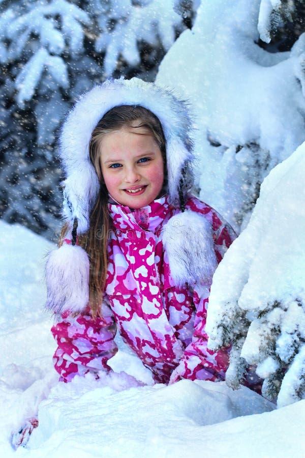 Övervintra med snö för barn som flickan i kläder nära träd parkerar in fotografering för bildbyråer